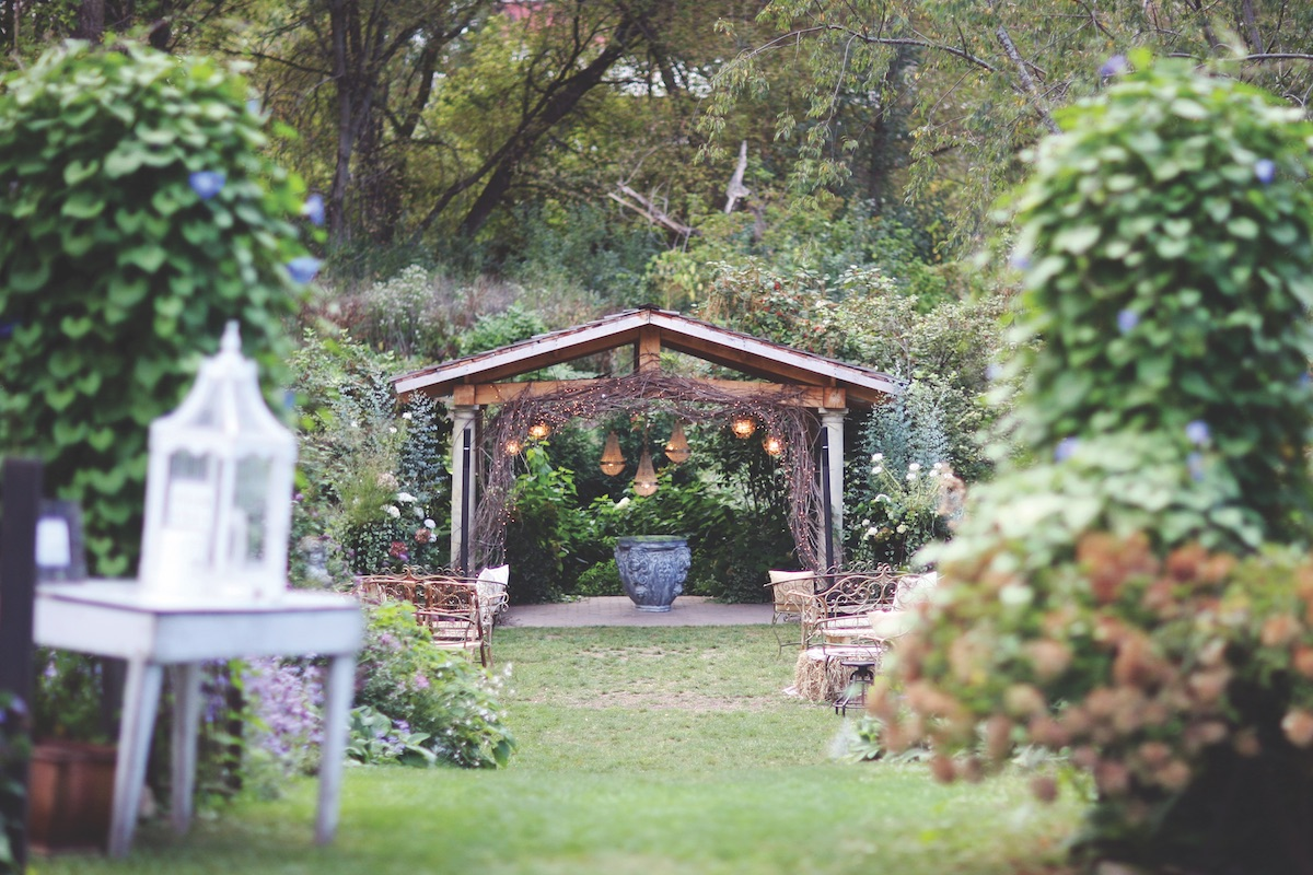 Rustic wedding ceremony set up with wood arm and wooden chairs