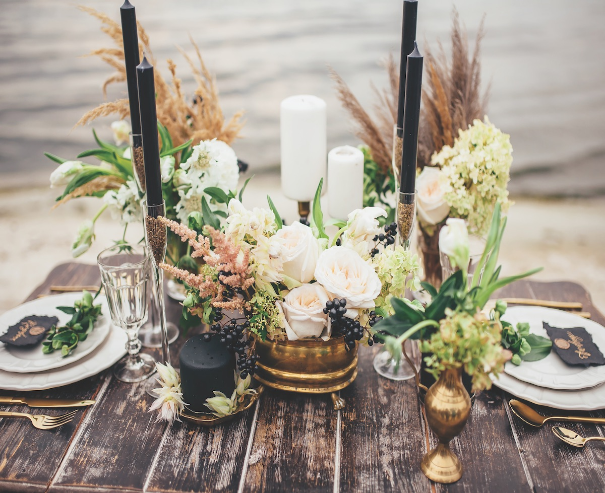 Modern rustic wedding decor with gold candle holders and black taper candles on a wooden table for two