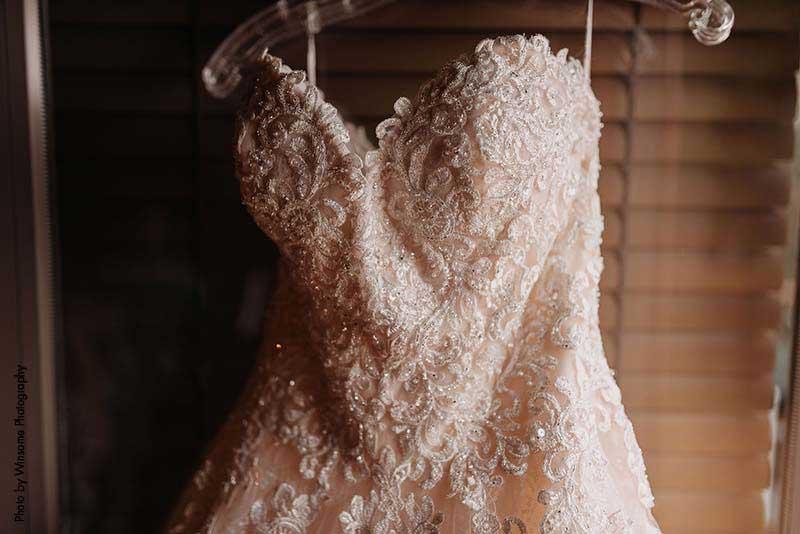 Bridal gown with sweetheart neckline hangs from door