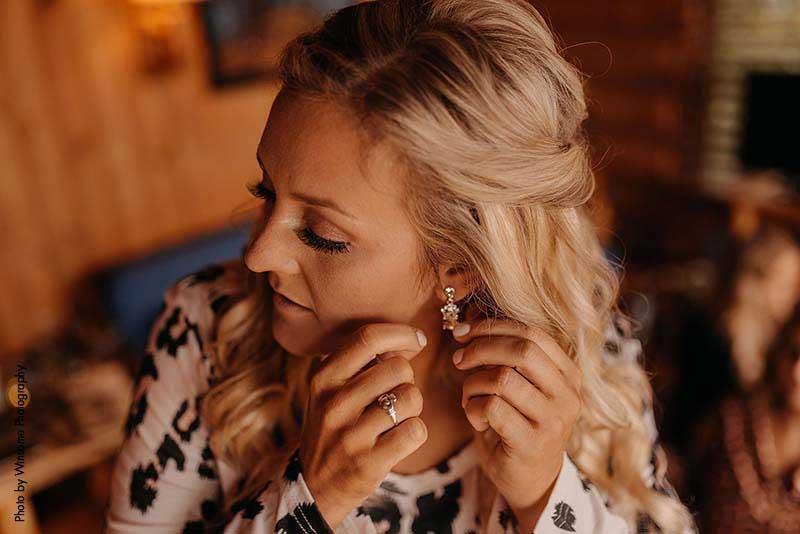 Bride puts on earrings before wedding