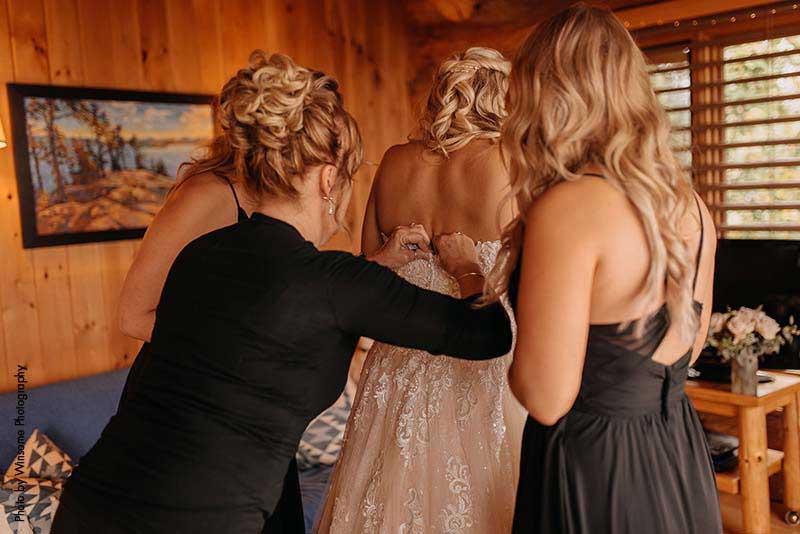 Bridesmaid and mother help bride zip up dress