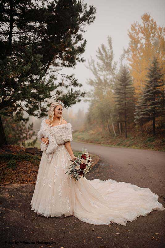 Bride in ballgown with fur wrap at outdoor fall wedding