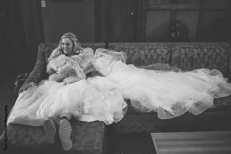 Bride sits on couch with dress laid out
