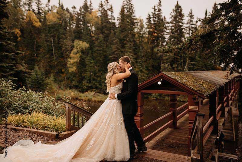 Bride and groom kiss outside Lutsen Resort