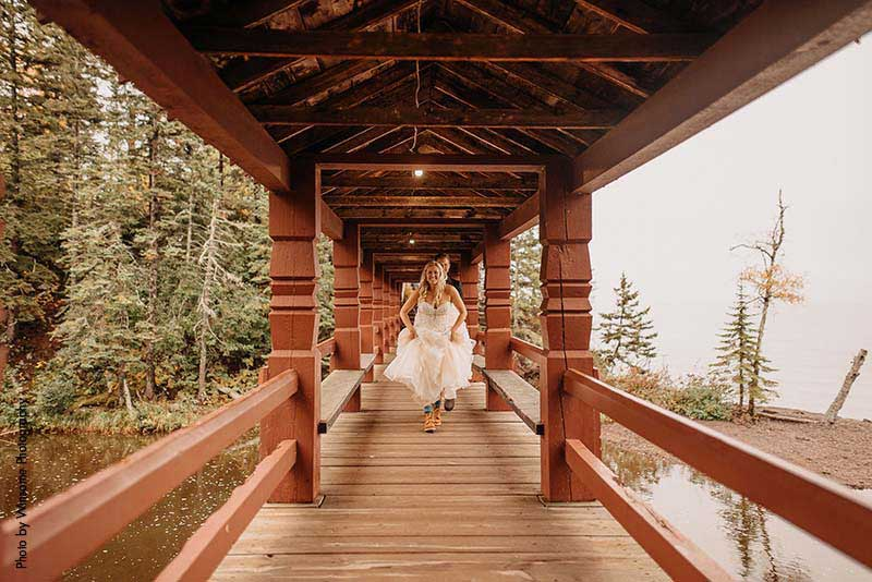 Bride runs across wooden bridge