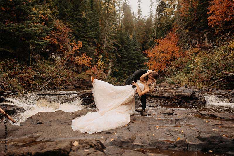 Bride in blush tulle ballgown kisses groom by river