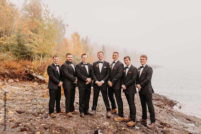 Groom stands with groomsmen in black suits