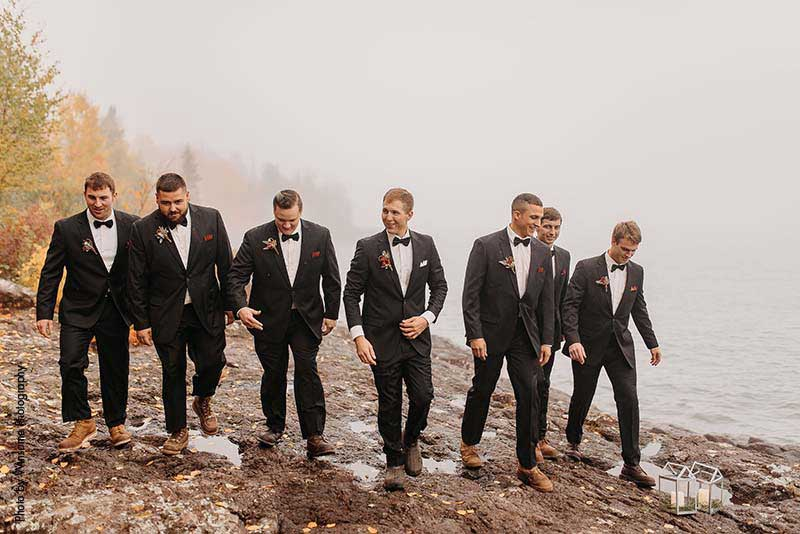 Groomsmen and groom in black suits walk along rocks on the North Shore in Minnesota