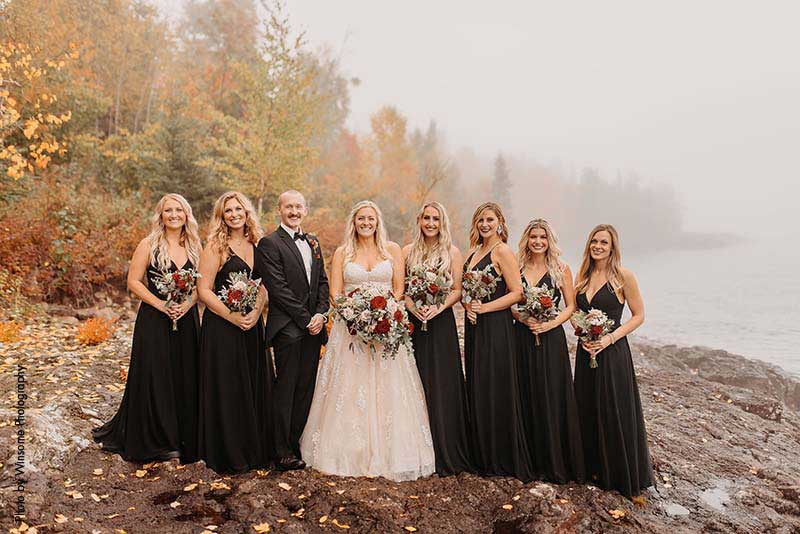 Bridesmaids and man of honor in black attire stand with bride on the North Shore