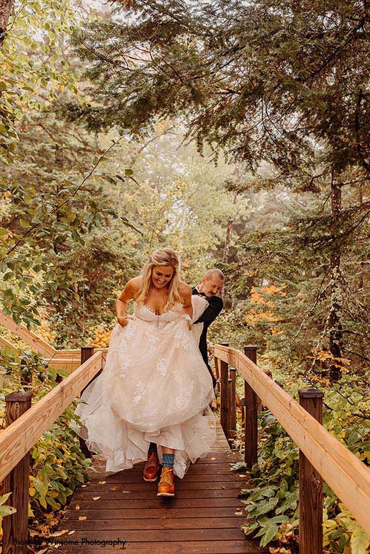 Bride in boots walks along bridge in the forest