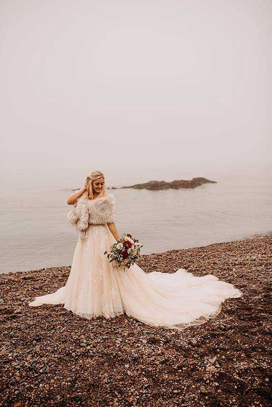 Bride stands on beach in sequin tulle ballgown