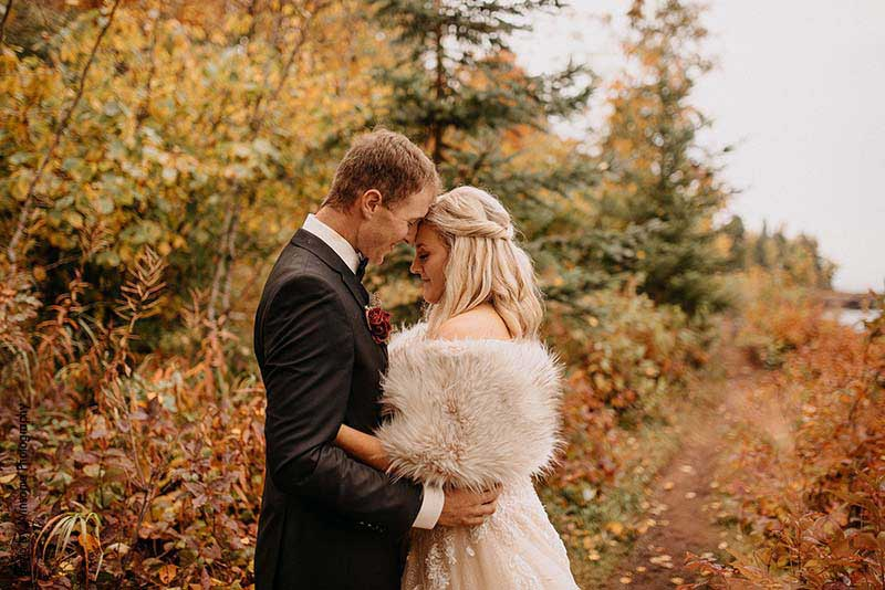 Bride and groom stand by trees with fall leaves