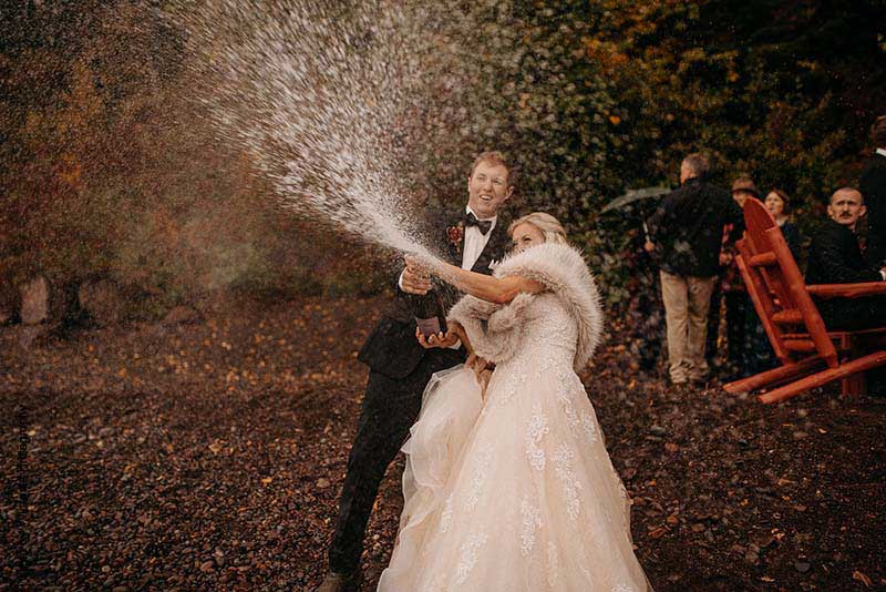 Bride and groom pop champagne