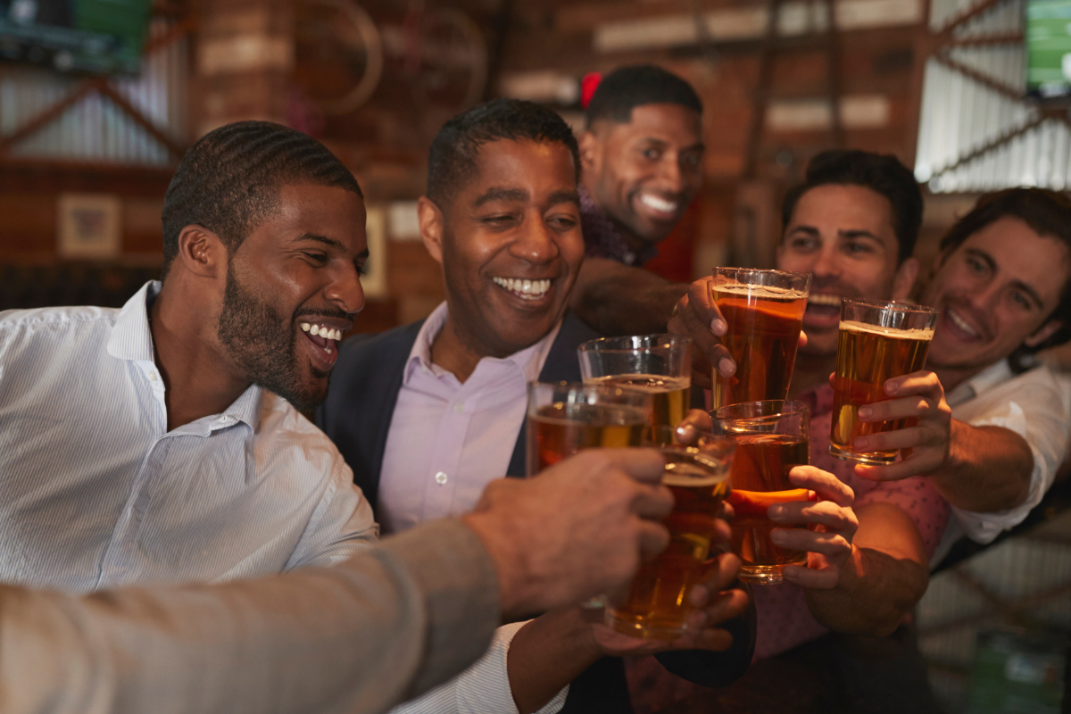 Men having a sophisticated bachelor party at a brewing while cheers-ing beers