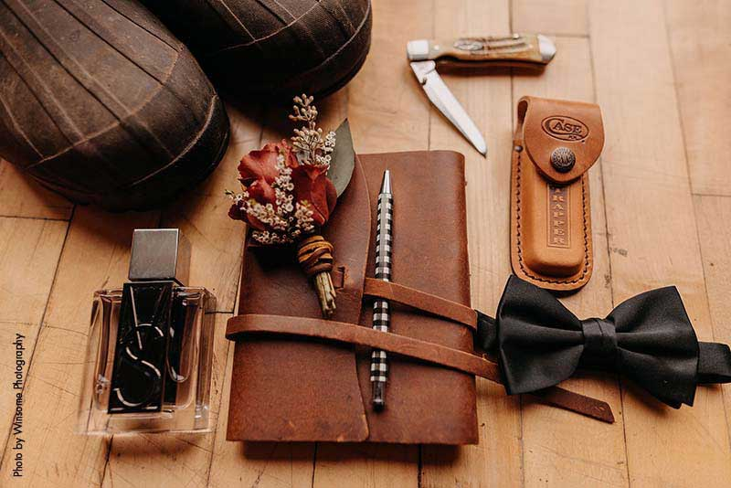 Groom's accessories with leather book, knife, bowtie, shoes