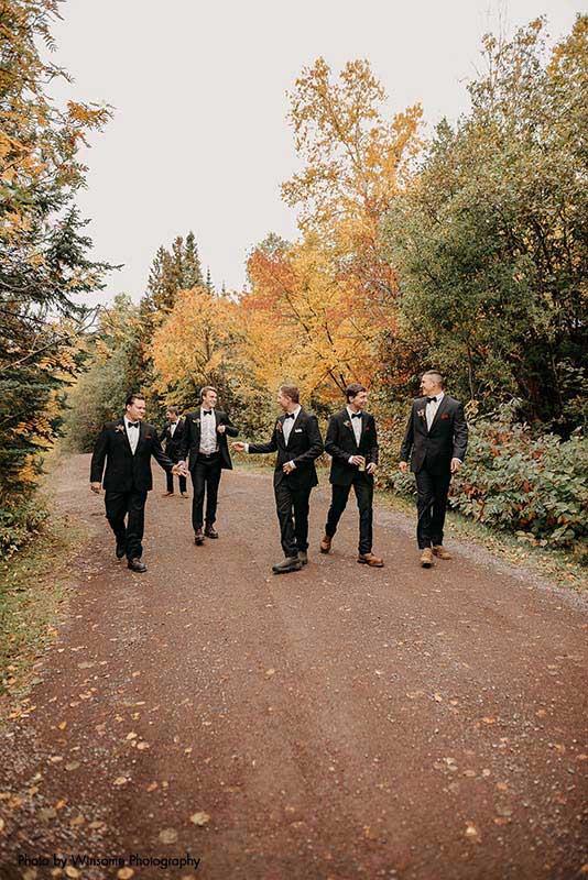 Groomsmen walk down dirt road