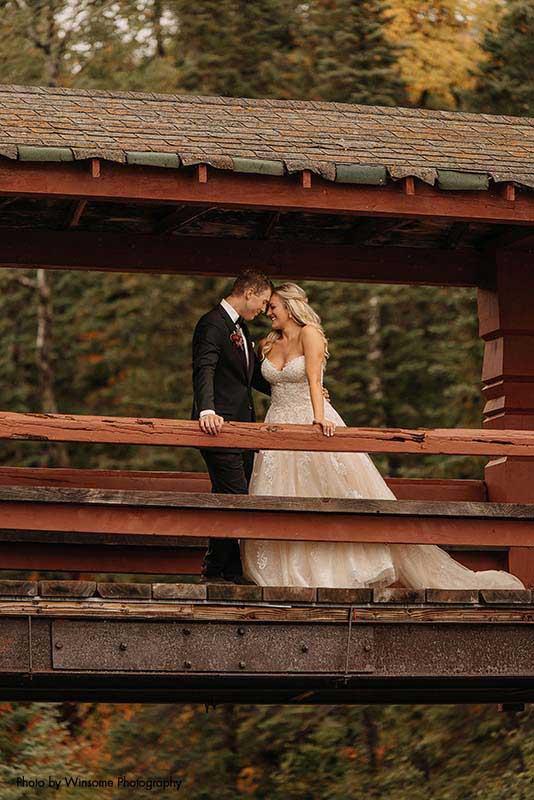 Bride and groom stand on bridge overlooking river