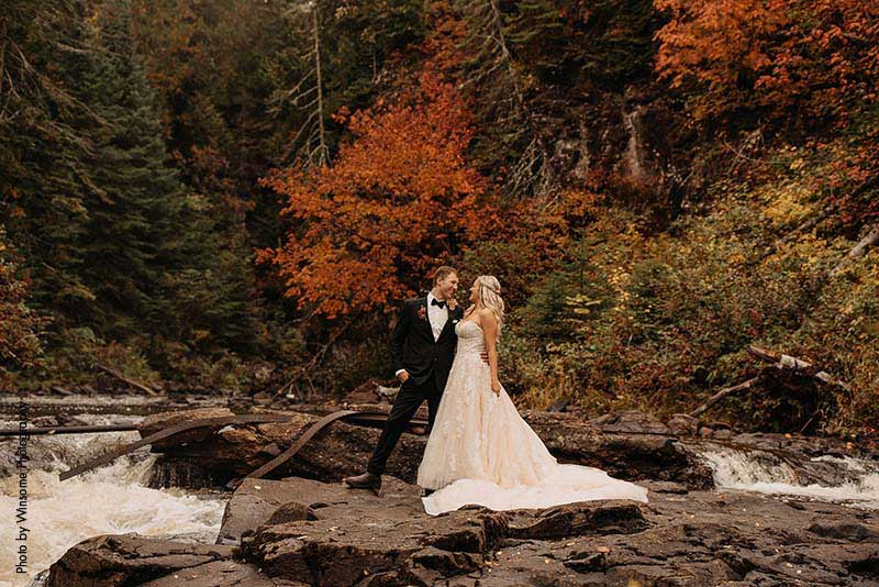 Bride and groom stand on rocks at fall wedding in Minnesota