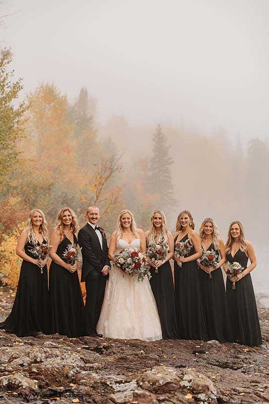 Bride stands with bridesmaids and man on honor in black dresses and suit