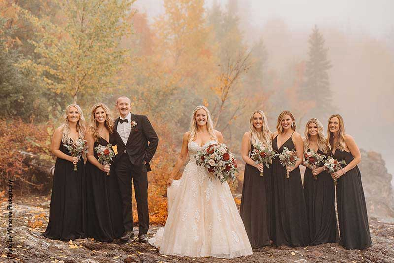 Bride stands with bridal party on the shores of Lake Superior