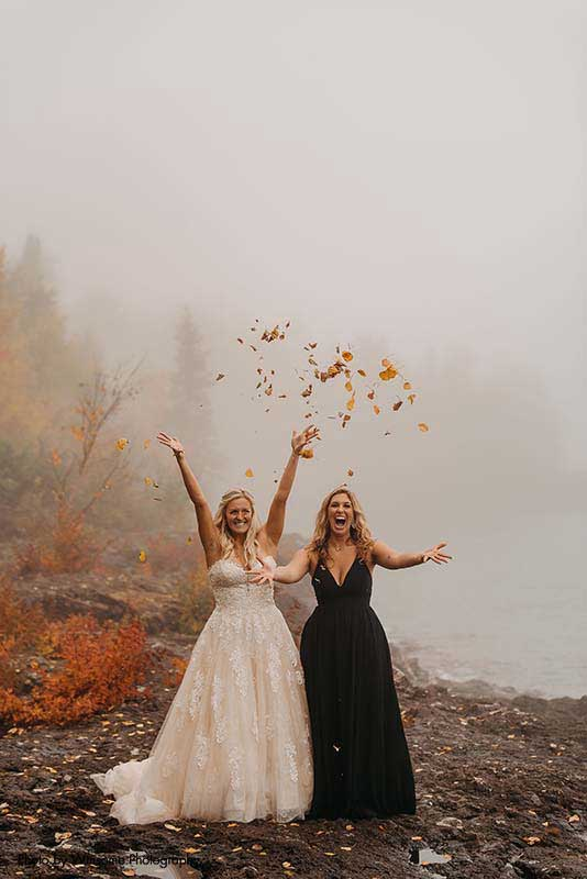 Bride and bridesmaid throw fall leaves into the air