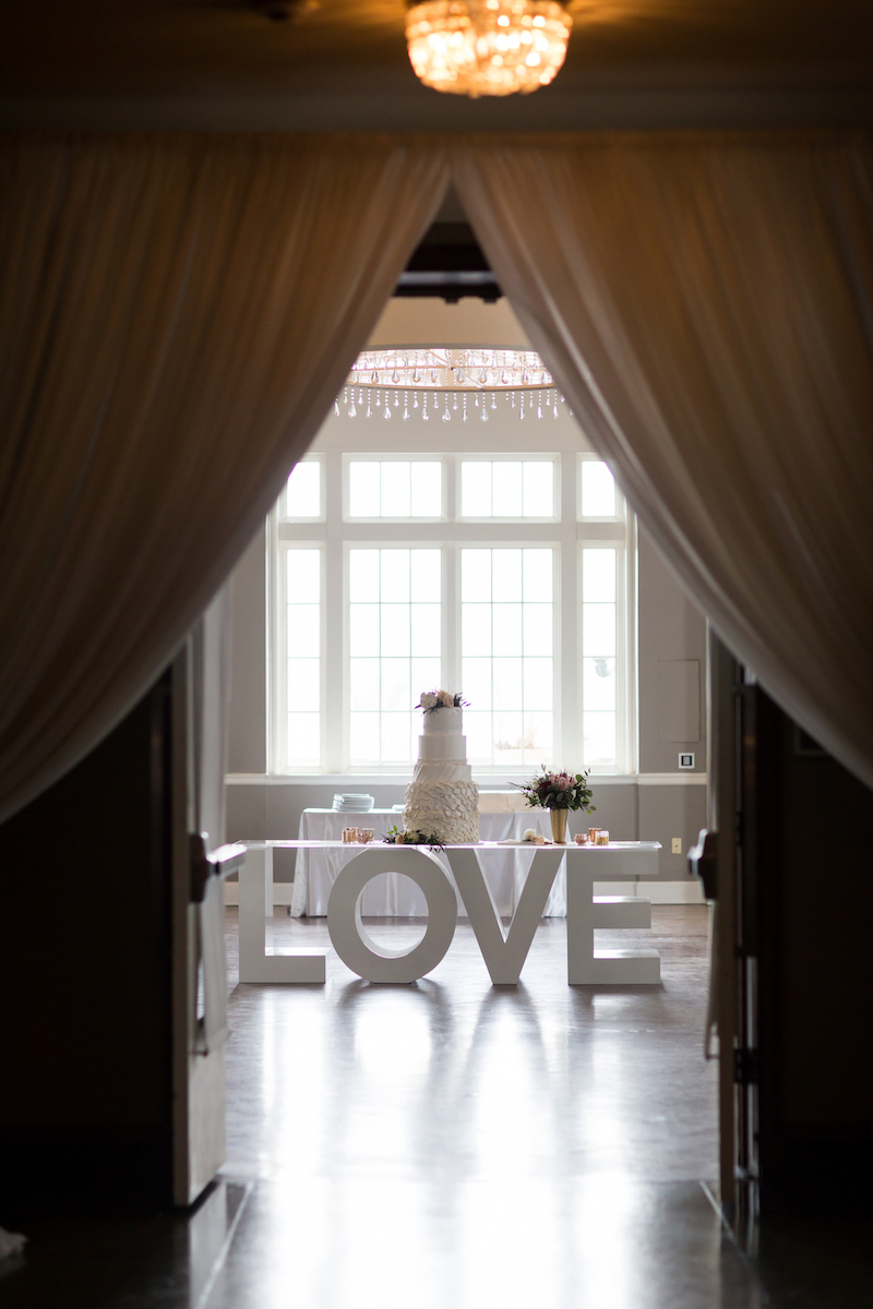 """Wedding reception entrance with chiffon drapes and large """"LOVE"""" letters"""