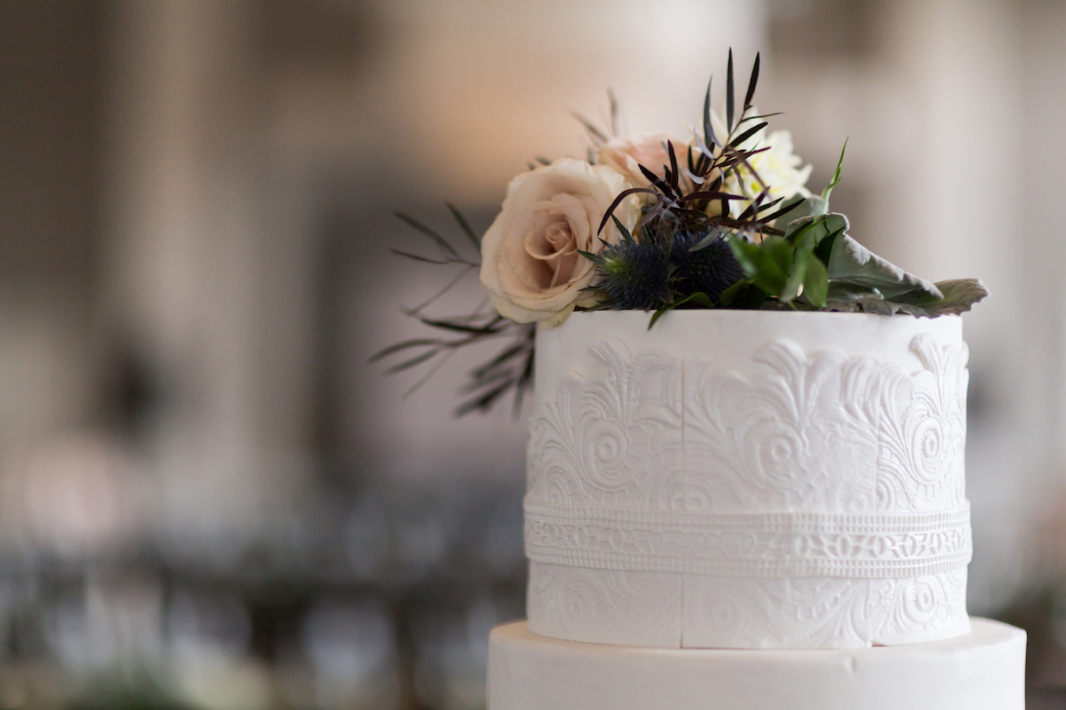 Intricate white wedding cake with floral and greenery atop