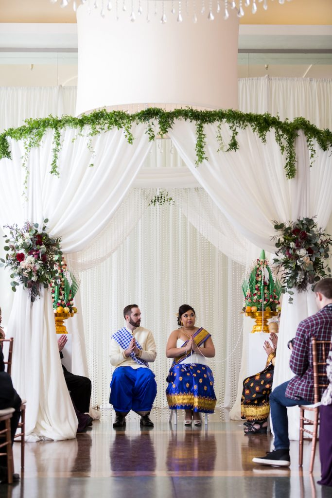 Laotian bride and groom sit under draped white arch