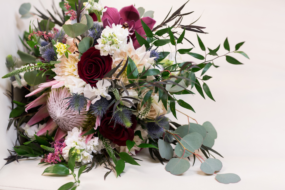 Bridal bouquet with greenery, purple, and dark red tones