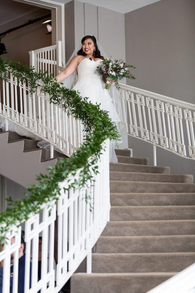 Bride in strapless gown walks down staircase