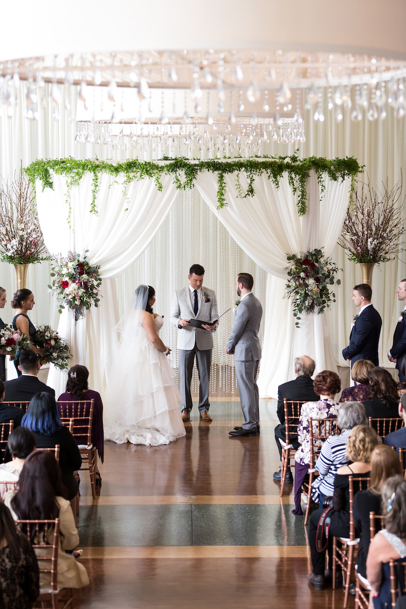 Couple stands under white draped arch with greenery