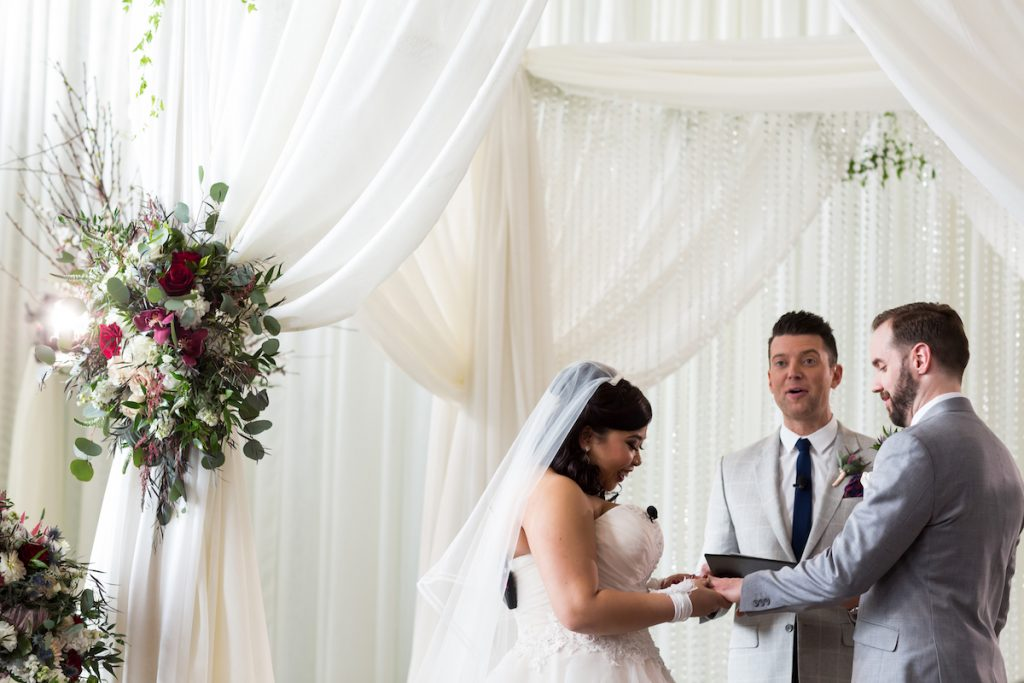 Bride and groom share vows under white draped arch