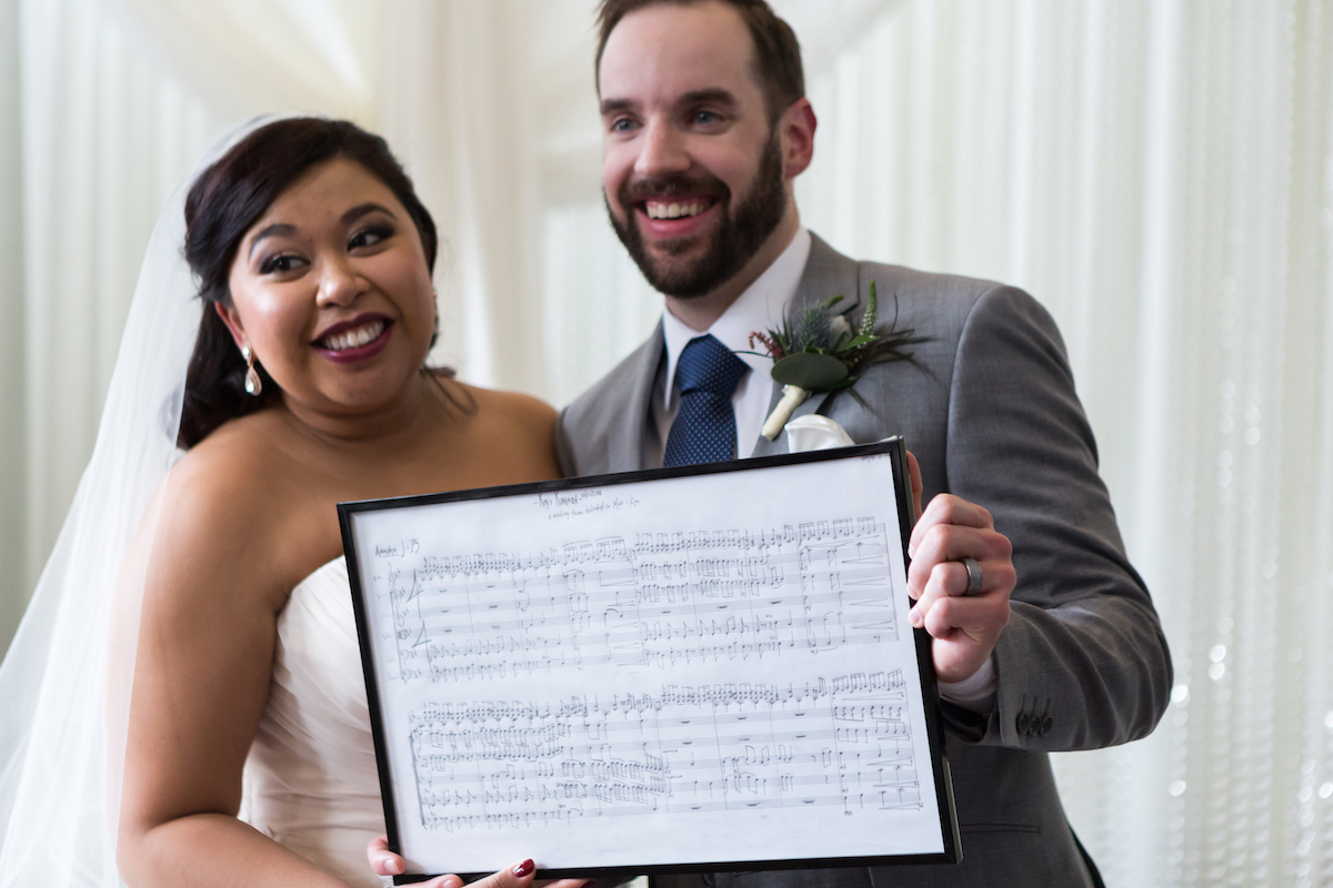 Couple holds wedding music in a frame