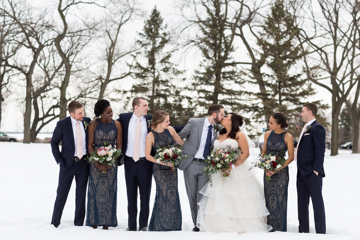 Bridal party stands outside in snow for winter wedding