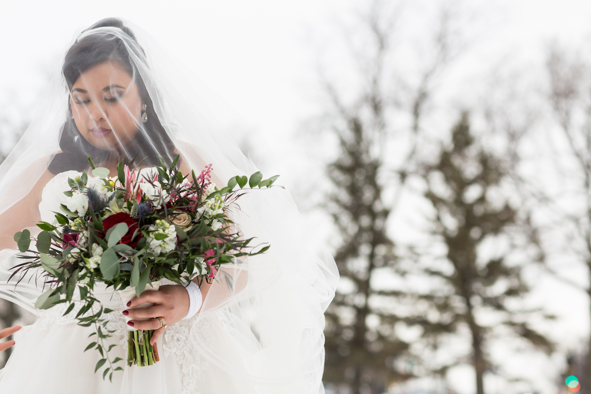 Winter bride stands outside with veil over face