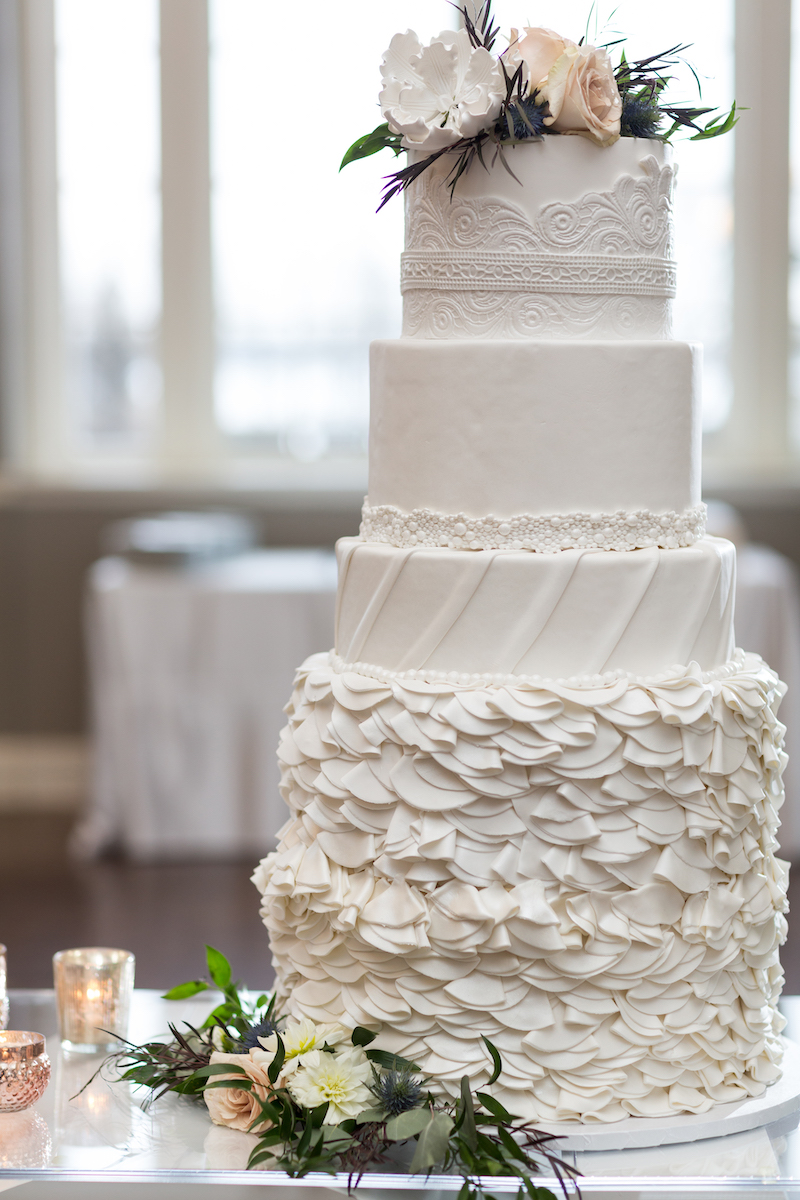 4-tier intricate white wedding cake with flowers and greenery on top