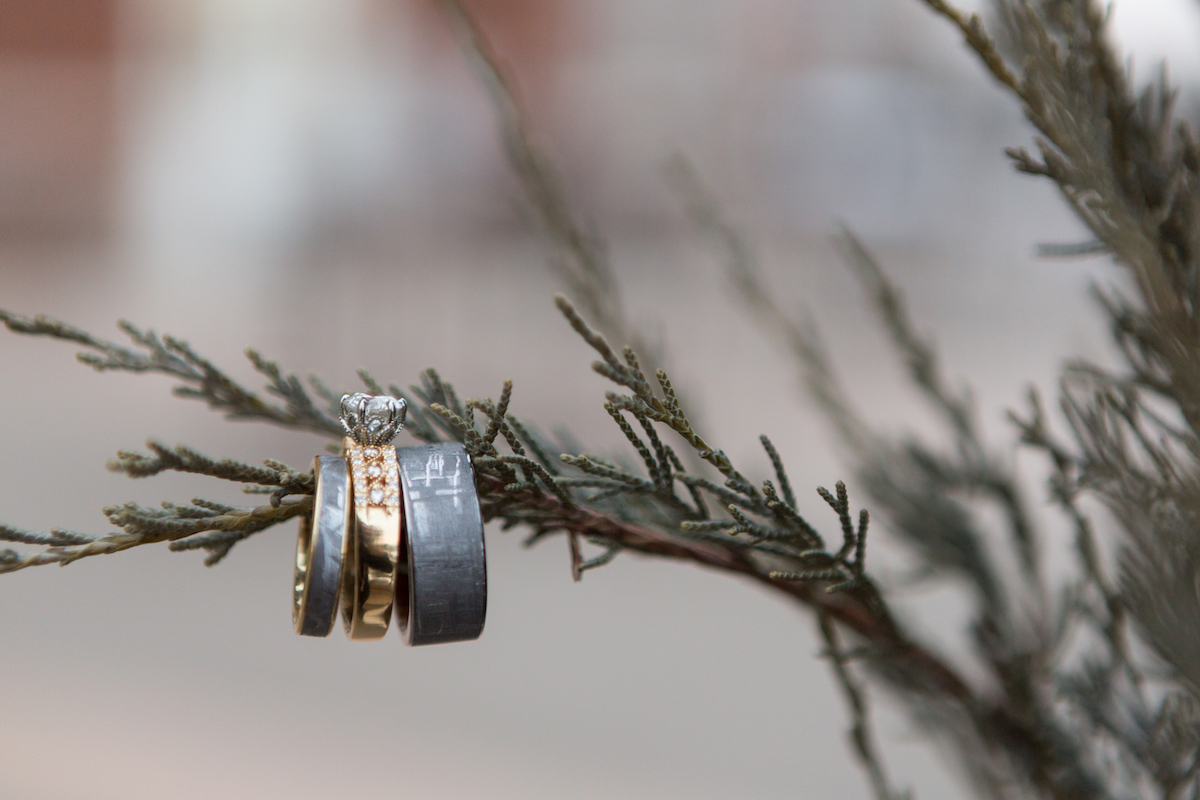 Gray wedding bands and rose gold engagement ring hang on pine tree