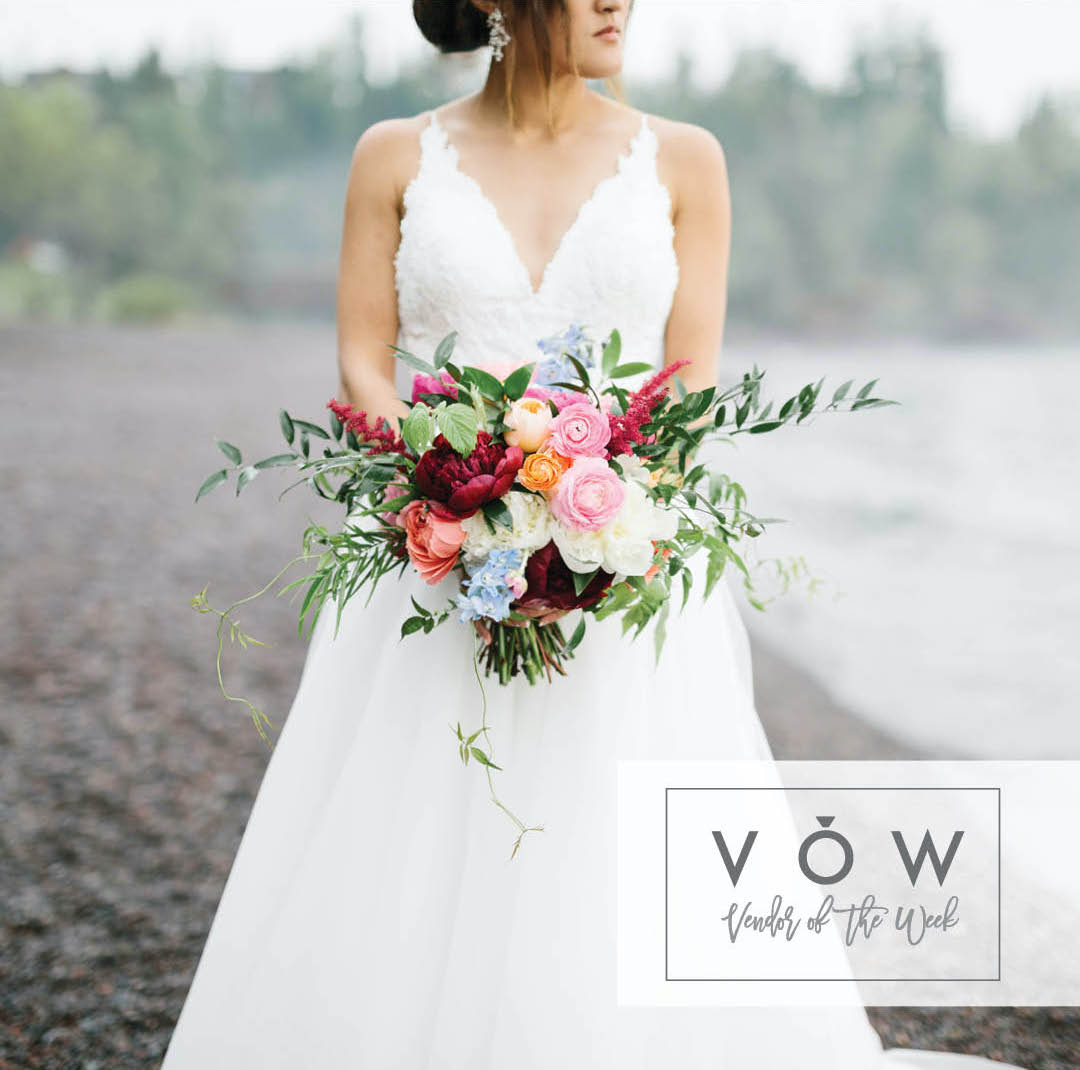 Bride stands on beach with bouquet at Lutsen Resort