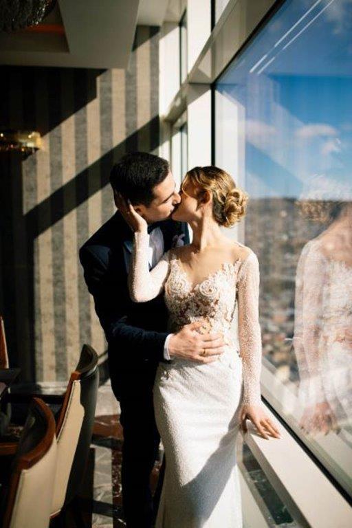 Man in custom black suit kisses bride in long-sleeve embellished bridal gosn
