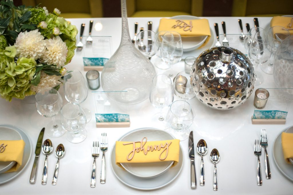 Modern and bright wedding tablescape with yellow napkins and chrome silverware and vases