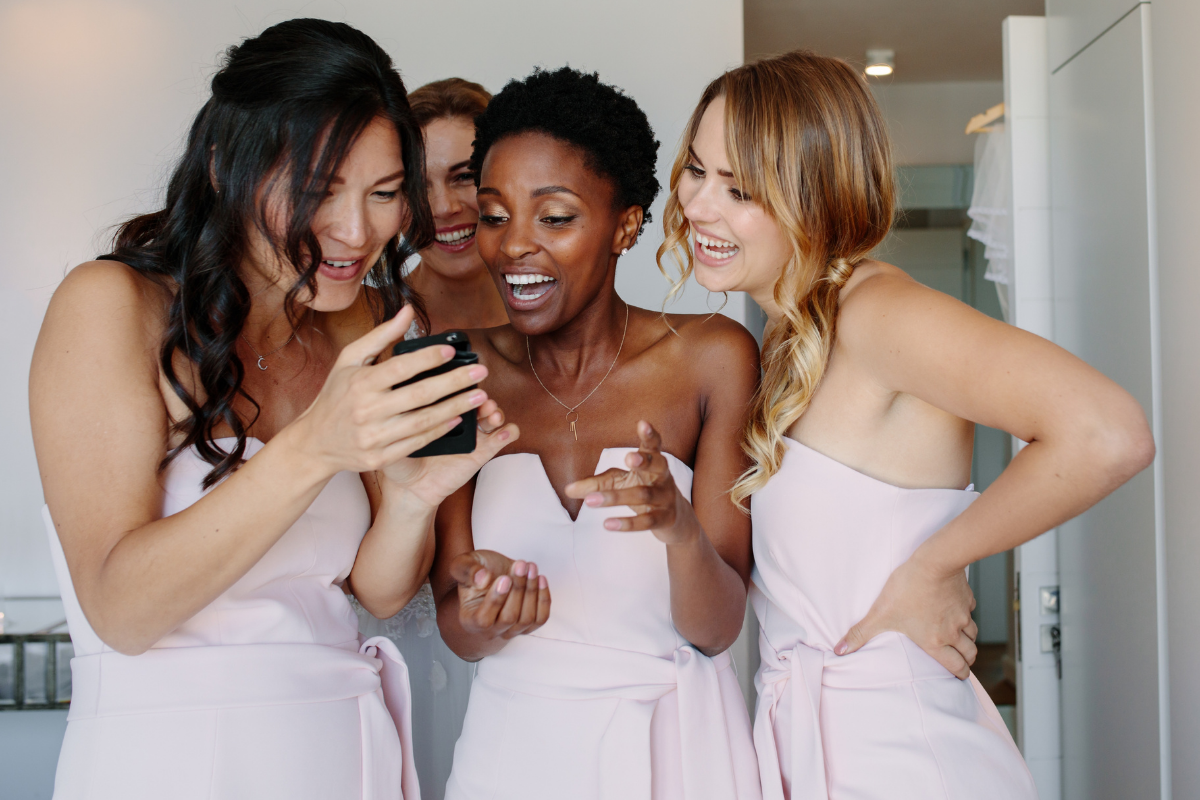 Bridesmaids take photo while getting ready