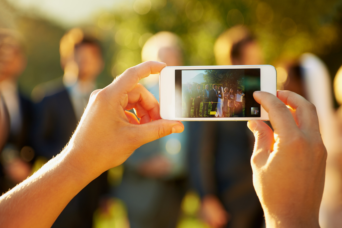 Guest takes image at wedding following wedding social media etiquette