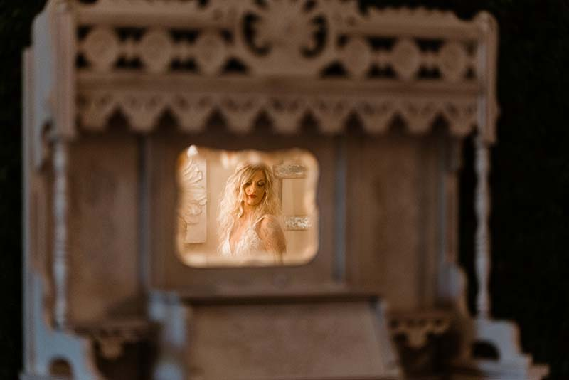 Bride looks in vintage mirror