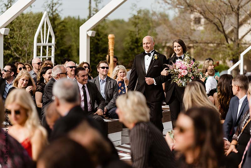 Father walks bride down aisle in outdoor ceremony