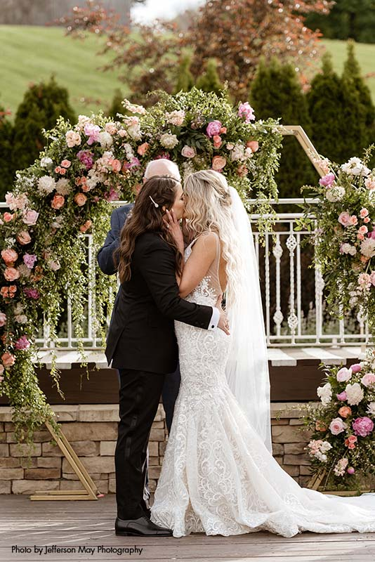 Brides kiss in front of floral geometric arch