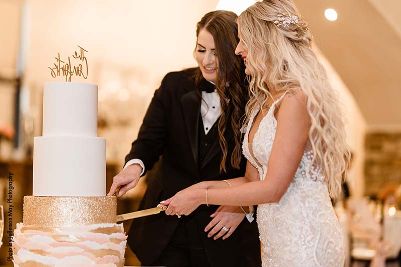 Brides cut wedding cake together