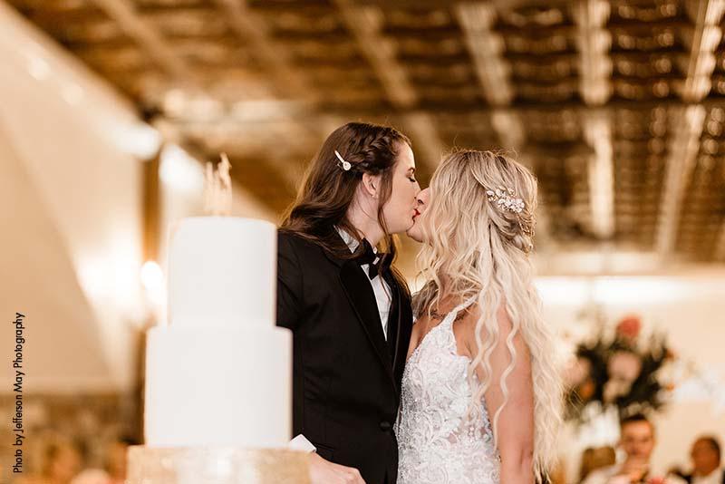 Brides kiss during cake cutting