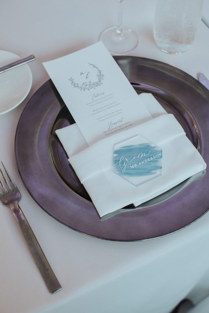 Summer wedding colors tabletop with purple charger and acrylic blue place cards