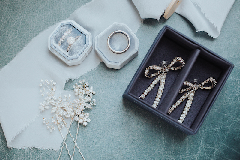 Luxury wedding accessory photo with diamond bow earrings, hair pins, and diamond engagement ring