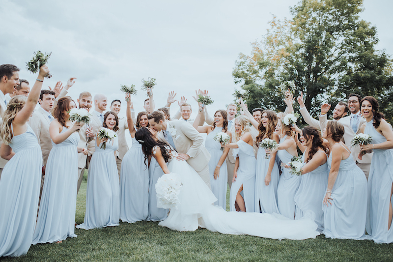 Bride in couture gown kisses groom in front of large bridal party in pale blue dresses